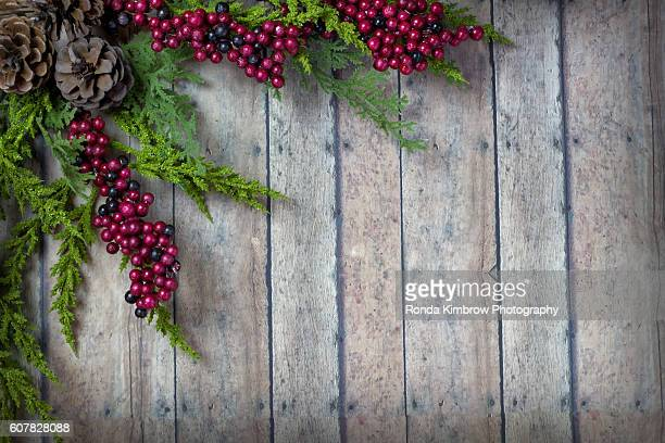 Christmas Garland with Pine Cones and Berries on a wood plank board with room for writing or text in the background