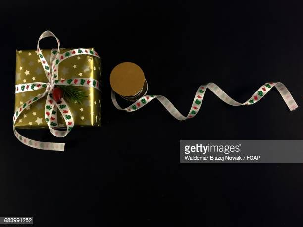 christmas gift and ribbon on black background - gift icon stock photos and pictures