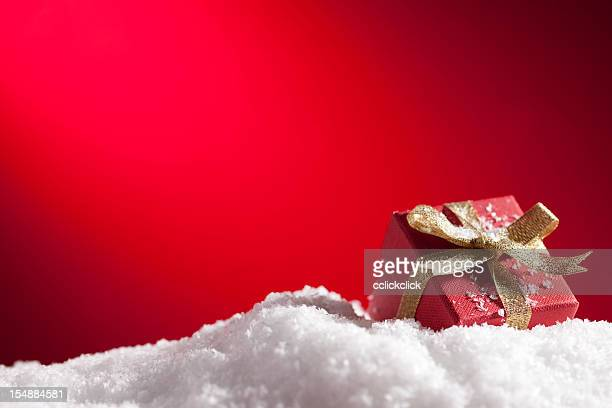 a christmas gift in snow with a red background - fake snow stock pictures, royalty-free photos & images