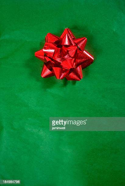 christmas gift; red bow on green wrapping paper