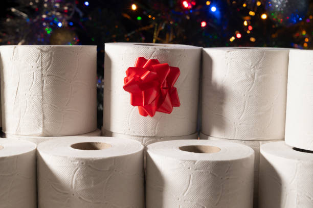 Christmas gift: toilet papers roles. In the background and out of focus, there is a Christmas tree decorated with colorful lights.