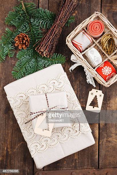 Christmas gift with gift tag and wrapping material on wooden table