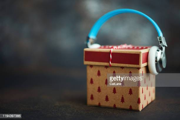christmas gift with headphones. gift of music - christmas music stock pictures, royalty-free photos & images