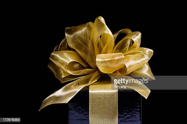 Christmas Gift Wrapped in Gold Ribbons, Bows on Black Background