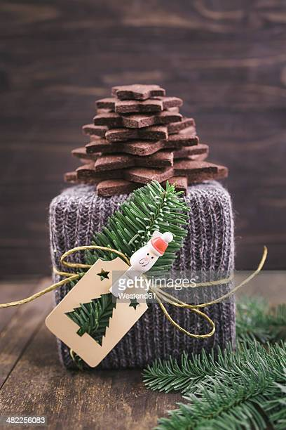 Christmas gift wrapped in knitted gift wrap with a Christmas tree made of chocolate sugar cookies