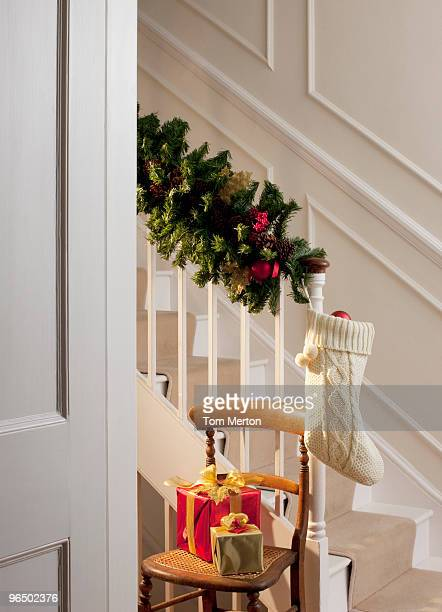 christmas gifts and stocking near staircase - christmas garland stock pictures, royalty-free photos & images