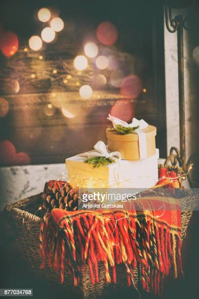 Christmas Gifts. Basket with boxes of gift, pine cone and blanket