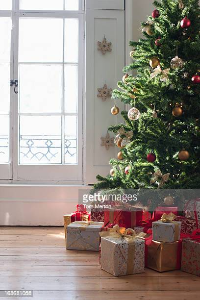 christmas gifts beneath tree near window - christmas gifts stock photos and pictures