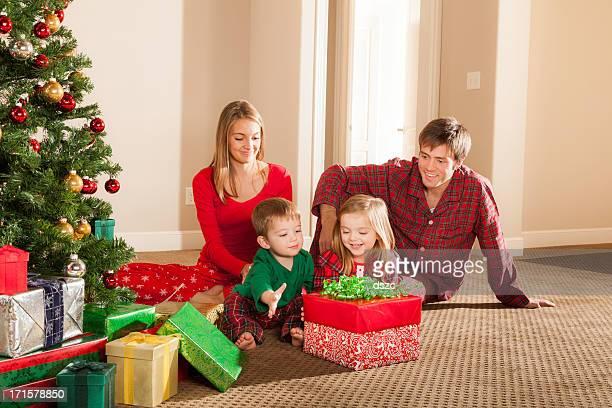 Jovem família abrindo presentes de Natal de manhã