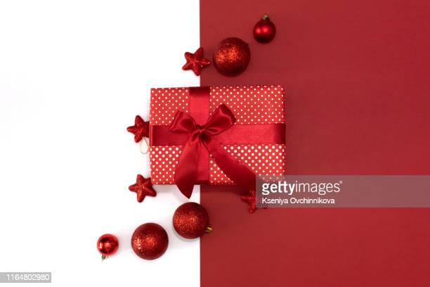 christmas gifts presents on red background. simple, classic, red and white wrapped gift boxes with ribbon bows and festive holiday decorations. - christmas past and christmas present stock pictures, royalty-free photos & images