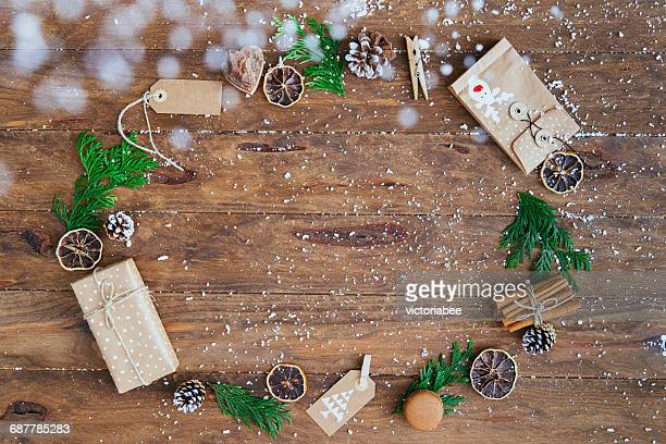 Christmas gifts, tags, pine cones, pine leaves, cinnamon sticks and dried orange slices in a circle