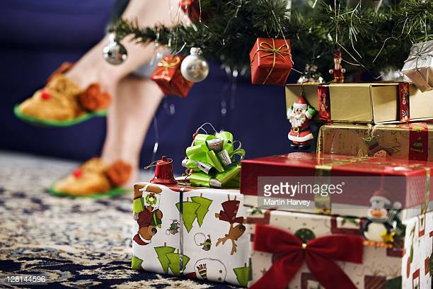 Christmas gifts under Christmas tree with reindeer slippers in background.
