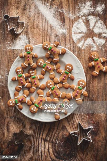 christmas gingerbread cookies on a wooden table with molds. - gingerbread man stock photos and pictures