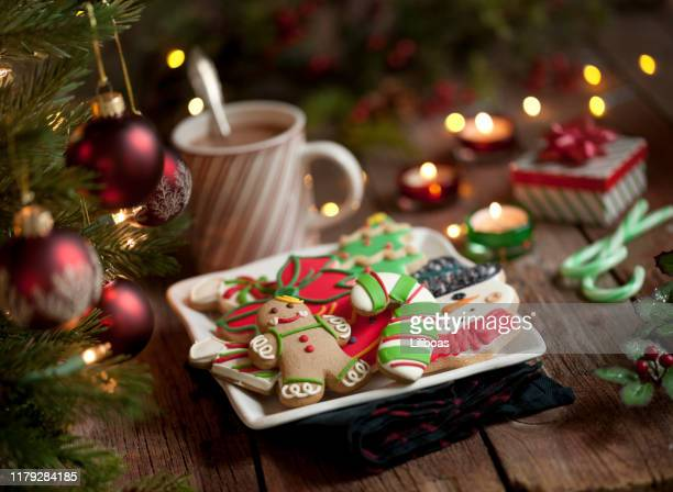 christmas gingerbread man and iced cookies on an old wood background - icing stock pictures, royalty-free photos & images