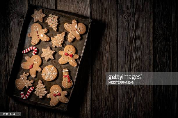 christmas gingerbread man cookies on vintage baking tray snowman, stars, snowflake, candy cane, reindeer and fir - gingerbread cookie stock pictures, royalty-free photos & images