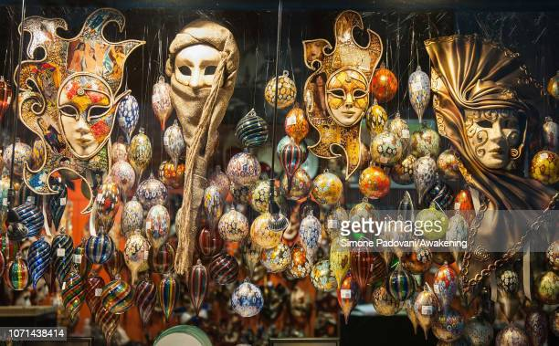 Christmas glass decorations made in Murano and carnival masks are seen on December 10 2018 in Venice Italy