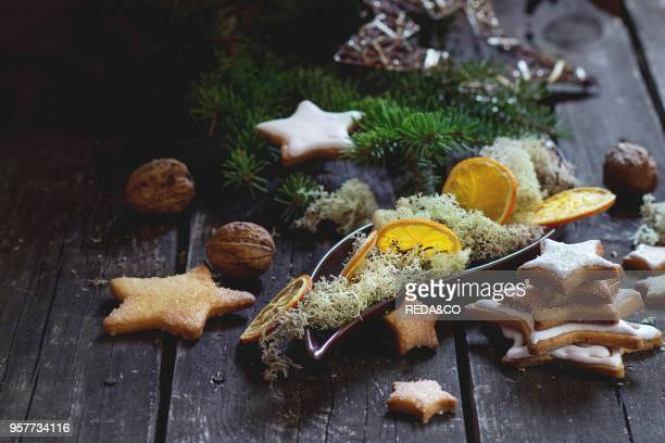 Christmas glazed star shapes cookies with Christmas tree moss and dry sliced orange in ceramic plate over red wooden table Dark rustic style day...