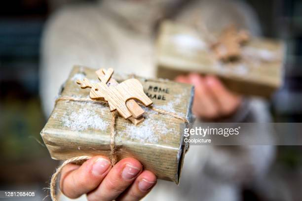 christmas: hands holding homemade christmas present. - home made stock pictures, royalty-free photos & images