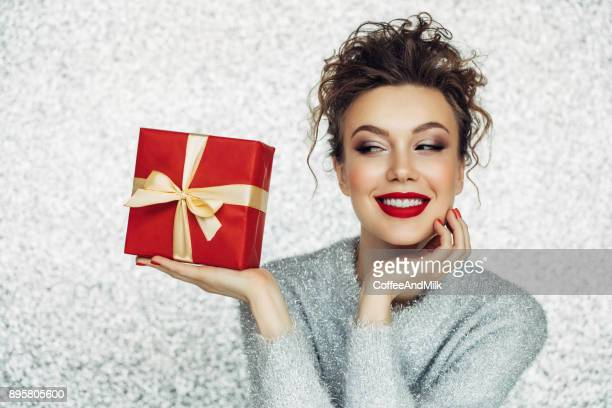 christmas happy smiling young woman holds gift box in hands - red lipstick stock pictures, royalty-free photos & images