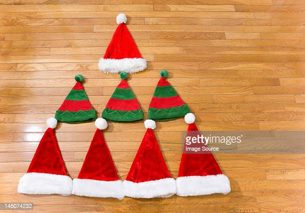 christmas hats in shape of christmas tree - floorboard stock photos and pictures