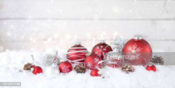 christmas holiday baubles against a snowfall and an old wooden background - country christmas stock pictures, royalty-free photos & images
