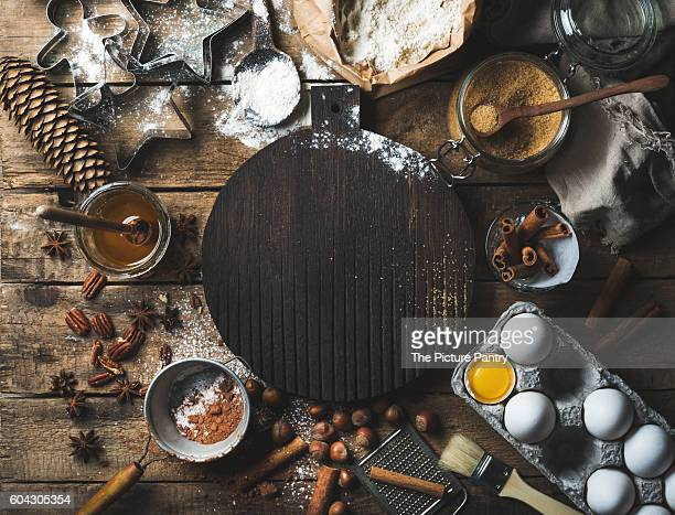 Christmas holiday cooking and baking ingredients on rustic wooden background with dark wood board in center