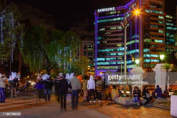 christmas in colombia - people seen outside the hacienda santa barbara mall in usaquén in the andean capital city of bogotá;  led lights decorate the trees. carrera séptima with regular traffic in front. - barbara carrera foto e immagini stock