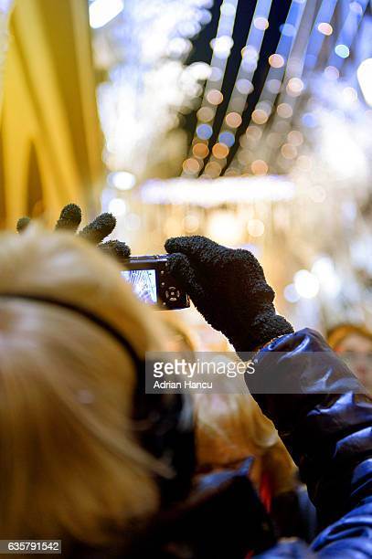 Christmas in France Adult woman wearing earmuffs and taking a picture on a compact mirrorless camera