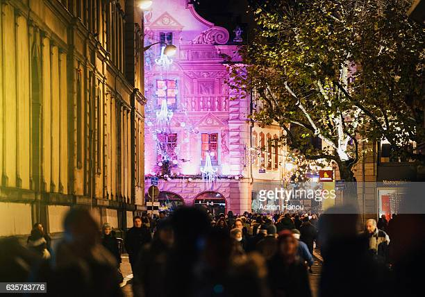 Christmas in France Crowd passing by the purple-illuminated and painted facade of the iconic Christian patisserie