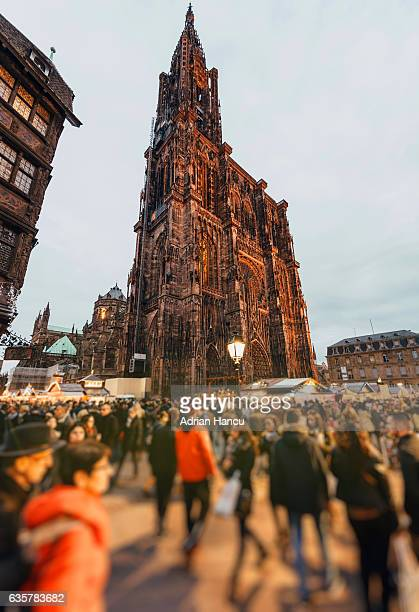 christmas in france passersby walking to and from the christmas market in the place de la cathedrale - strasbourg stock pictures, royalty-free photos & images