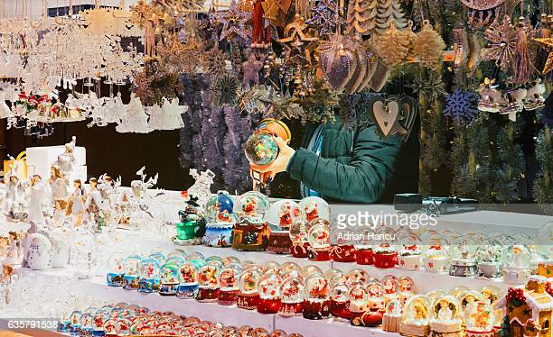 Christmas in France Salesperson checking on snowball toys on the stand