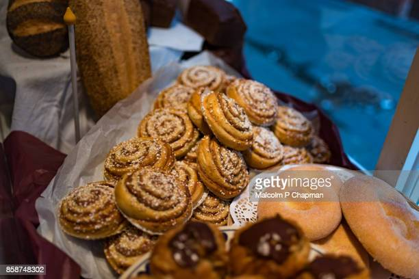 christmas in sweden - cinnamon buns in bakery display - swedish culture stock pictures, royalty-free photos & images