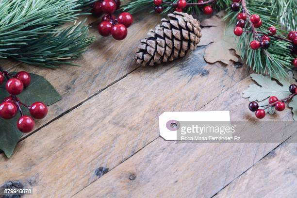 Christmas item, blank greeting card and pine cone on rustic wooden background framed with mistletoe seed, leaves and fir tree branches. Selective focus and copy space