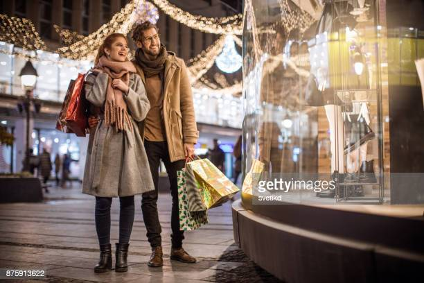 christmas joy of shopping - christmas scenes stock photos and pictures