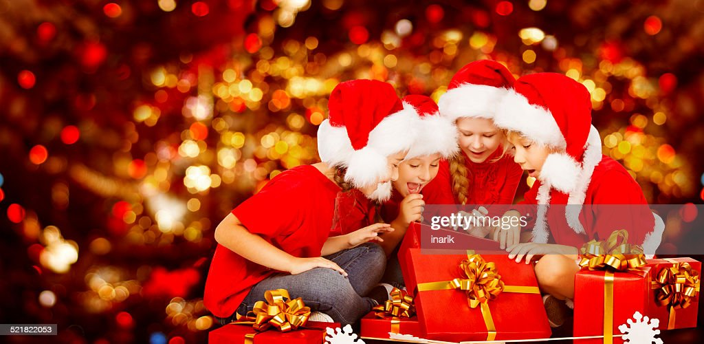 Christmas Kids Opening Present Gift Box Children In Santa Hat Stock ...