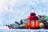 Christmas lantern in snow with fir tree branch. Winter cozy scene for New Year holidays.