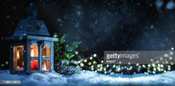 christmas lantern with lit candle on snow - christmas decore candle stock pictures, royalty-free photos & images