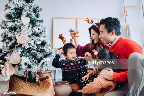 christmas lifestyle theme. happy asian family decorating christmas tree together in the living room at home. they are putting on various baubles and ornaments and enjoying their holiday - asia stock pictures, royalty-free photos & images