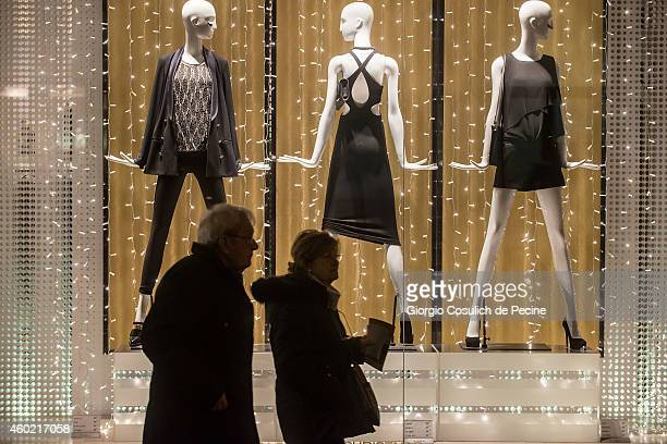 Christmas lighting and decorations adorn a store window in a crowded street of down town area on December 9 2014 in Rome Italy
