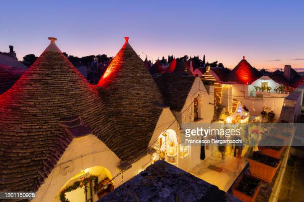 christmas lights and decorations during dusk in the monumental site of trulli. - alberobello foto e immagini stock
