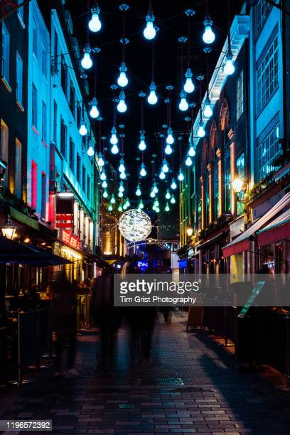 christmas lights and revellers in carnaby street at night, soho, london, uk. - west end london stock pictures, royalty-free photos & images