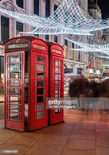 christmas lights and shoppers with red telephone boxes on a london street at night - red telephone box stock pictures, royalty-free photos & images