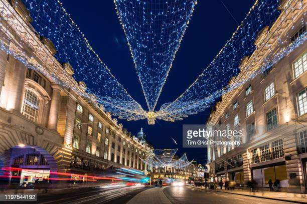 christmas lights and traffic on regent street at night, in london's west end, uk. - tim grist stock pictures, royalty-free photos & images
