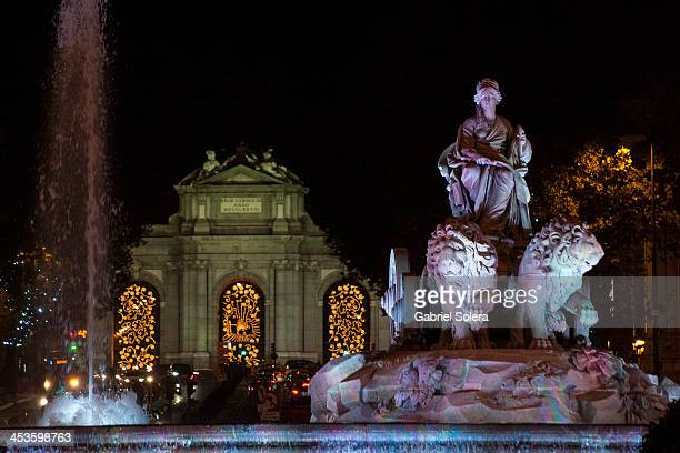 Christmas lights illuminate the Cibeles Fountain and the Puerta de Alcala on December 4 2013 in Madrid Spain Each holiday season designers are...