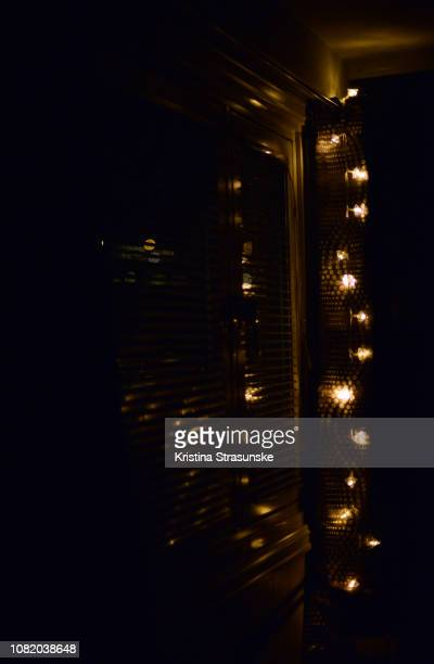 christmas lights in a window at night - kristina strasunske stock photos and pictures