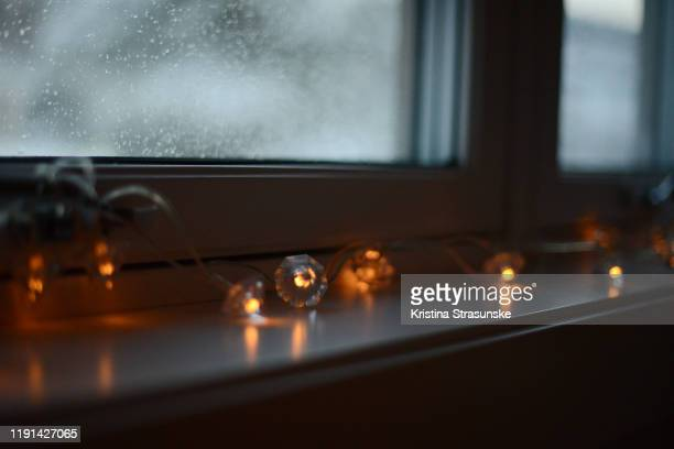 christmas lights in a windowsill on a rainy day - kristina strasunske stock pictures, royalty-free photos & images