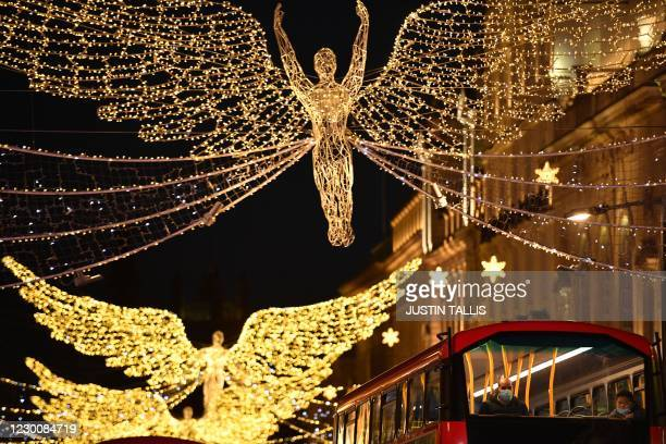 Christmas lights twinkle as passengers travel in a bus along Piccadilly, London on December 12 as with under two weeks to Christmas, people take...