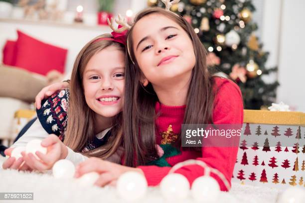 Christmas little girls in front of a Christmas tree
