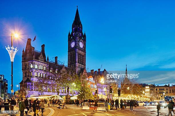 Christmas market by town hall illuminated at night, Manchester, UK