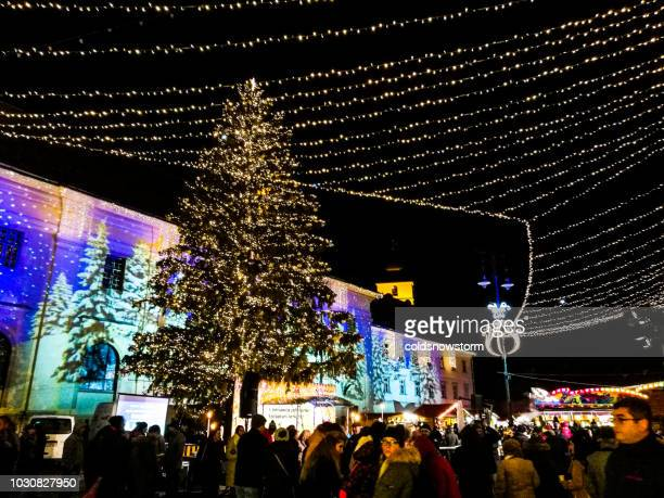 christmas market illuminated at night in sibiu, transylvania, romania - sibiu stock photos and pictures